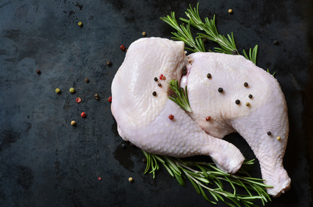 Raw chicken legs on a black background.