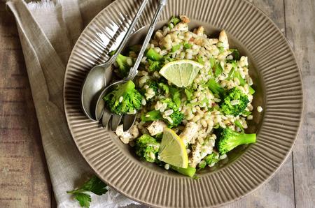 Warme salade van gerst, broccoli en gebakken kip op rustieke achtergrond. Stockfoto