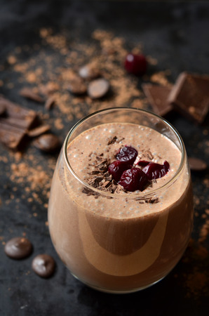 Delicious chocolate smoothie Black forest with cherry on dark table.