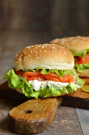 food on table: Healthy burger with salted salmon and cream cheese on rustic background. Stock Photo