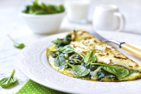 Frittata farcito con spinaci e formaggio per una colazione. Archivio Fotografico - 50852236