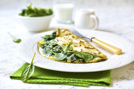 Omelet gevuld met spinazie en kaas voor een ontbijt.