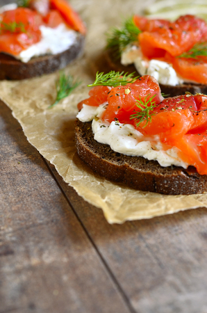 sandwish: Sandwich with salted salmon and cream cheese on rustic background.