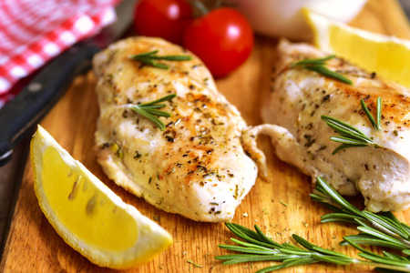 Chicken baked with rosemary on a cuuting board.