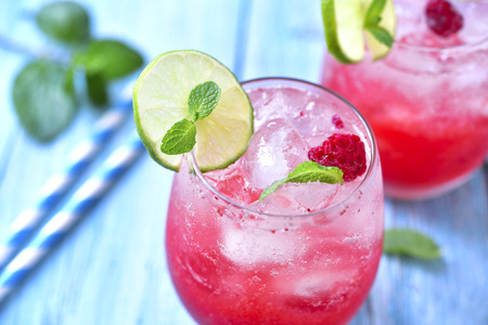 Raspberry lemonade with lime in a glass on a blue wooden background.