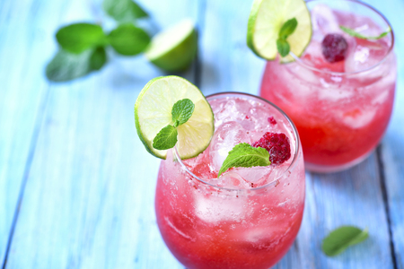 Raspberry lemonade with lime in a glass on a blue wooden background. Zdjęcie Seryjne - 51622103