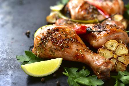 Grilled spicy chicken legs on a black background.
