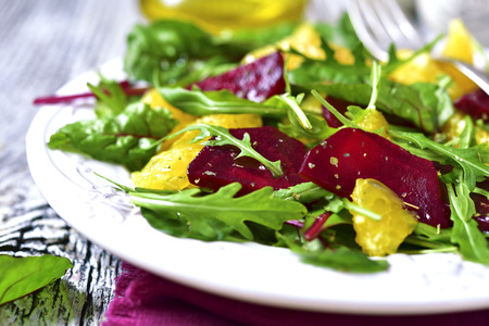 Fresh salad from greens,beetroot and orange on rustic background.
