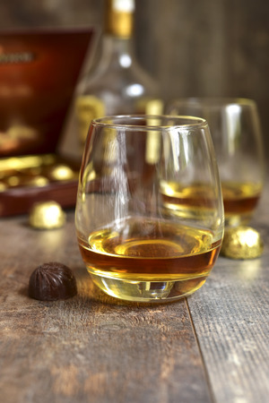 cognac: Glass of cognac with chocolate candy.