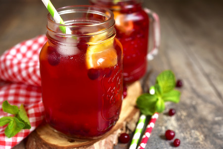 Iced cranberry tea with orange in a mason jar on rustic background. Фото со стока