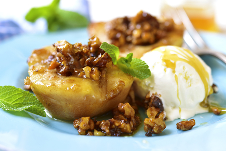 Grilled pear with caramelized walnuts and honey on a blue vintage plate.