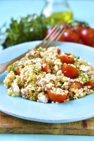 Quinoa salad with cherry tomatoes and chicken on a blue background.
