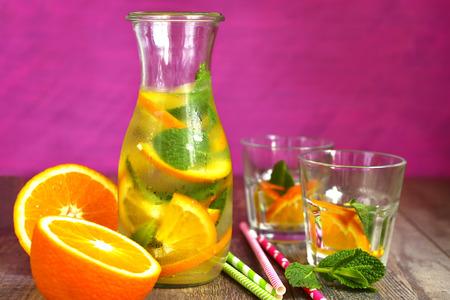 limonada: limonada de naranja en una botella sobre un fondo rosa. Foto de archivo