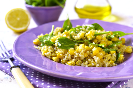 Quinoa salad with spinach and sweet corn on a purple plate.Vintage style.