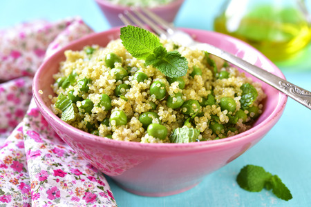 Quinoa salad with green pea and mint on a light  blue background.