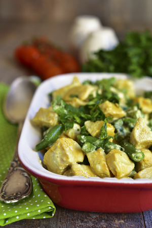 fricassee: Chicken curry with asparagus bean on a rustic background. Stock Photo