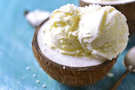 glace: Ice cream in a coconut on a blue wooden table.