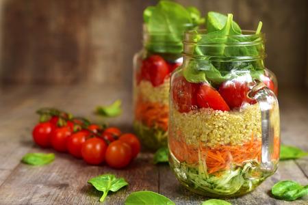 Salade met quinoa en groenten in een metselaarkruik op een rustieke houten achtergrond. Stockfoto