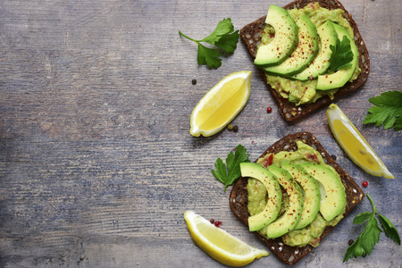 Delicious wholewheat toast with guacamole and avocado slices.Mexican cuisine. Фото со стока - 56491771