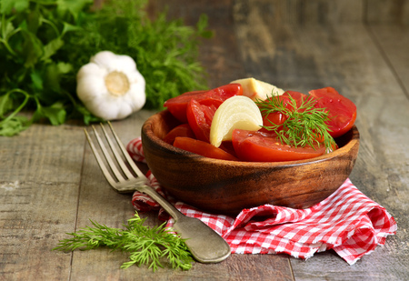 marinated: Homemade marinated tomatoes in a wooden bowl. Stock Photo