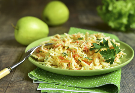 Coleslaw with apple on a green plate on ruatic background.
