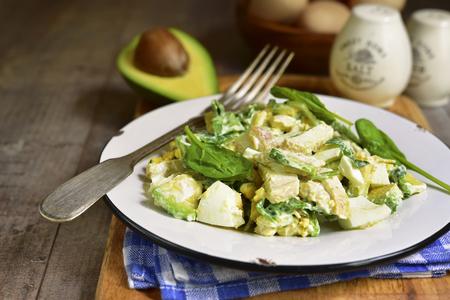 アボカド、ゆで卵、ほうれん草、鶏木造背景にビンテージ プレートの素朴なサラダ。 写真素材