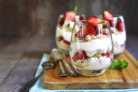 Delisious traditional english dessert eton mess with strawberry on a wooden background. 스톡 콘텐츠