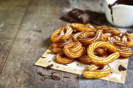 churros: Traditional mexican dessert churros with chocolate sause on a rustic background.