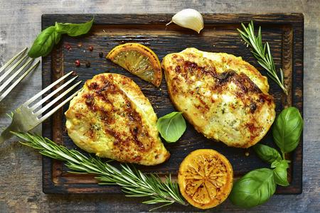Geroosterde kruidige kippenborst met kruiden op oude scherpe raad De achtergrond van het voedsel Hoogste mening.