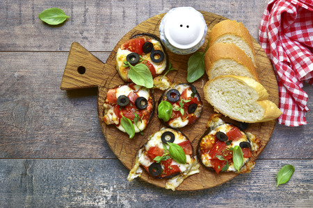 lying on leaves: Pizza on a eggplant slices.Top view. Stock Photo