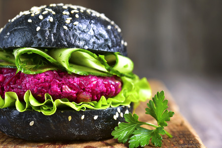 Vegan black burger with beetroot on a cutting board on rustic wooden background.