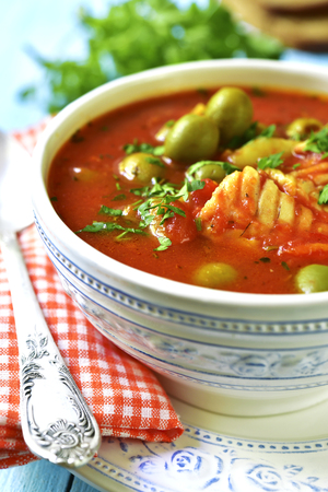 potato cod: Tomato soup with cod,potato and olives in a vintage bowl.