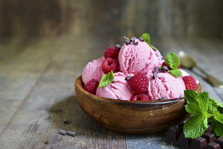 Homemade raspberry ice cream in a wooden bowl on a rustic background. Archivio Fotografico