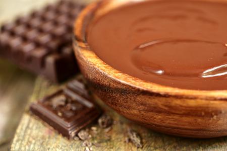 ganache: Chocolate ganache in a wooden bowl on rustic background.