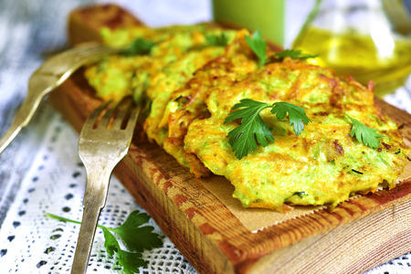 Zucchini fritters with garlic and carrot on a rustic wooden background.
