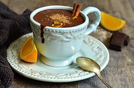 Homemade hot chocolate with orange and cinnamon in a vintage cup. Stock Photo