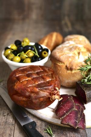antipasti: Assortment of italian antipasti on a cutting board on a wooden table.