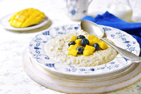 baby rice: Oat porridge with mango and blueberry for a breakfast on a light background.Vintage style. Stock Photo