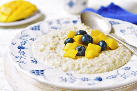 Oat porridge with mango and blueberry for a breakfast on a light background.Vintage style. Archivio Fotografico