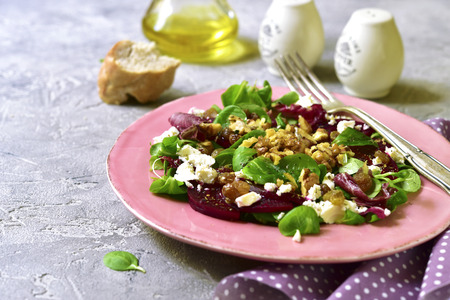 greeen: Beetroot salad with raisins,walnuts,feta and greeen leaves mix on a vintage plate on a grey concrete background. Stock Photo