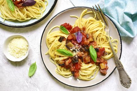 Spaghetti met aubergines en tomatensaus op een uitstekende plaat op lichte achtergrond Hoogste mening. Stockfoto