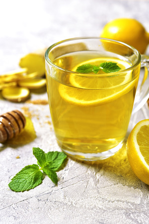 catarrh: Warming ginger tea with lemon and mint in a glass cup on grey concrete background.