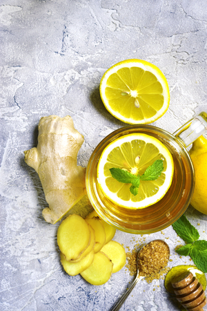 warming therapy: Warming ginger tea with lemon and mint in a glass cup on grey concrete background.Top view.