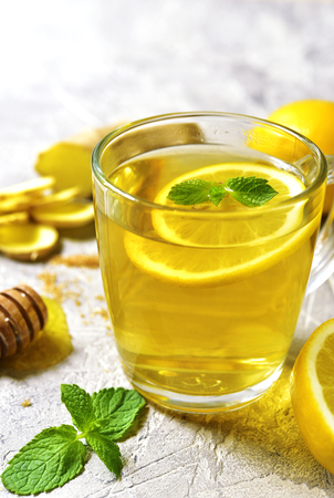 warming therapy: Warming ginger tea with lemon and mint in a glass cup on grey concrete background.