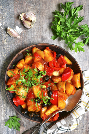Mediterranean potato ragout with bell pepper,garlic and olivesin tomato sauce  in a clay bowl on a rustic wooden background.Top view.