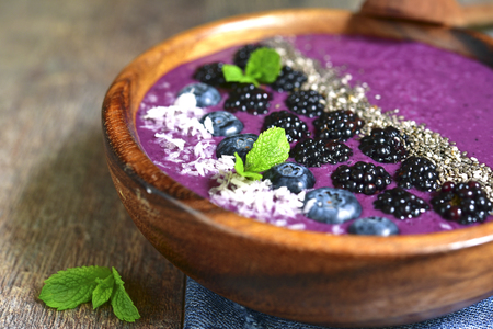 mulberry paper: Berry smoothie with chia seed in a wooden bowl on a rustic wooden background.Top view.