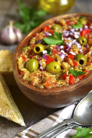 Rustic mediterranean eggplant salad with tomato,capsicum and garlic in a wooden bowl. Stock Photo