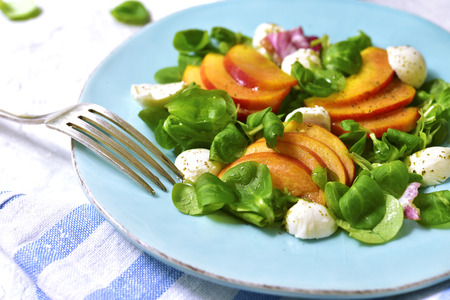 Fresh peach salad with corn and mozzarella on a blue plate on a concrete background.