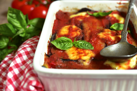 Traditional italian dish parmigiana with eggplants in a white baking form.