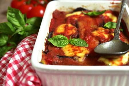 Traditionelle italienische Gericht parmigiana mit Auberginen in einem weißen Backform. Standard-Bild - 64202264